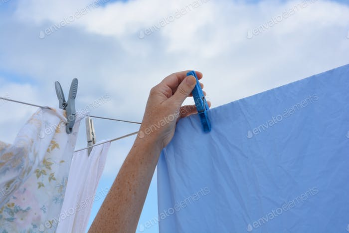 Woman using laundry on the clothesline to dry in the sun, using plastic clothespins