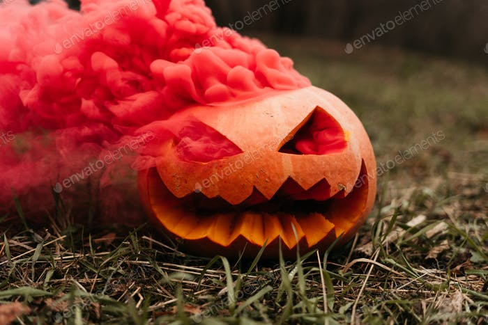 Spooky pumpkin with red smoke on Halloween Jack o lantern