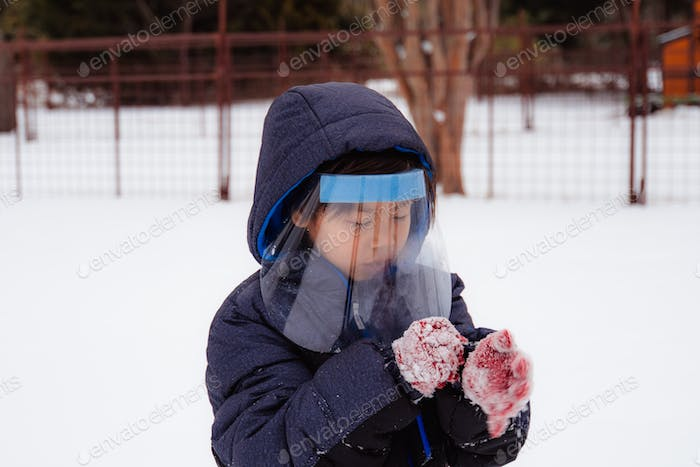 Young boy In the snow with PPE gear
