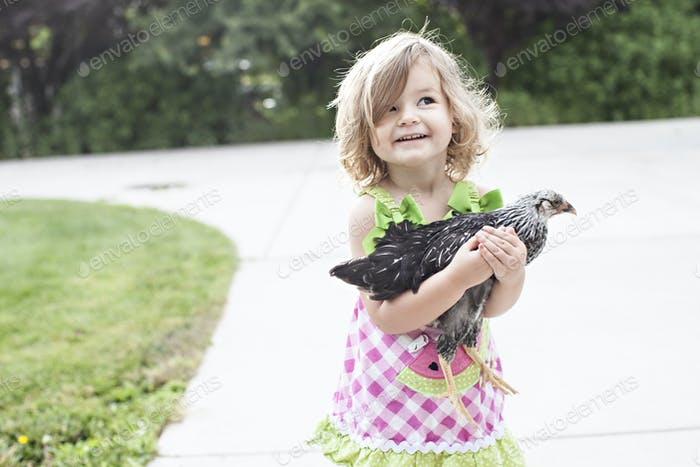 little girl holds a chicken in her arms