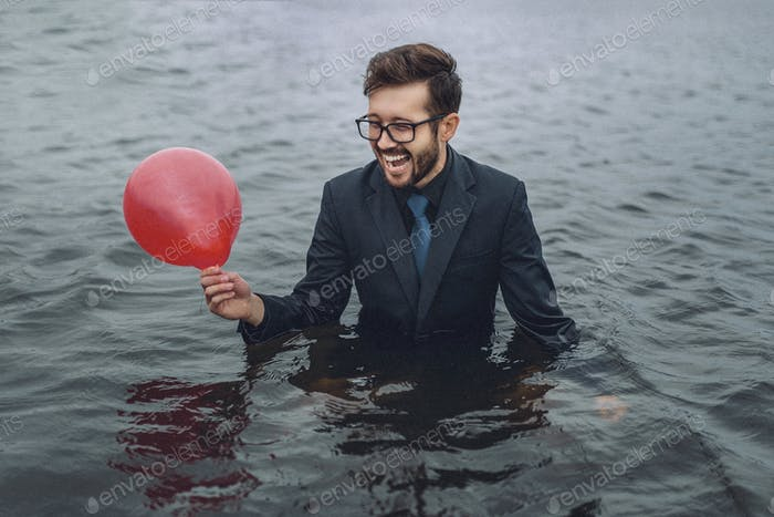 the clerk in a jacket and glasses stands waist-deep in water with a red balloon in his hand and