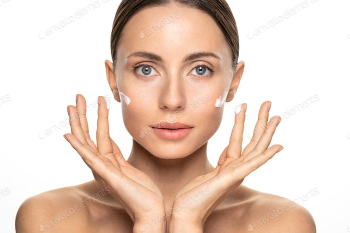 Woman with flawless skin applying nourishing cream on her face cheek and fingers. Skin care.