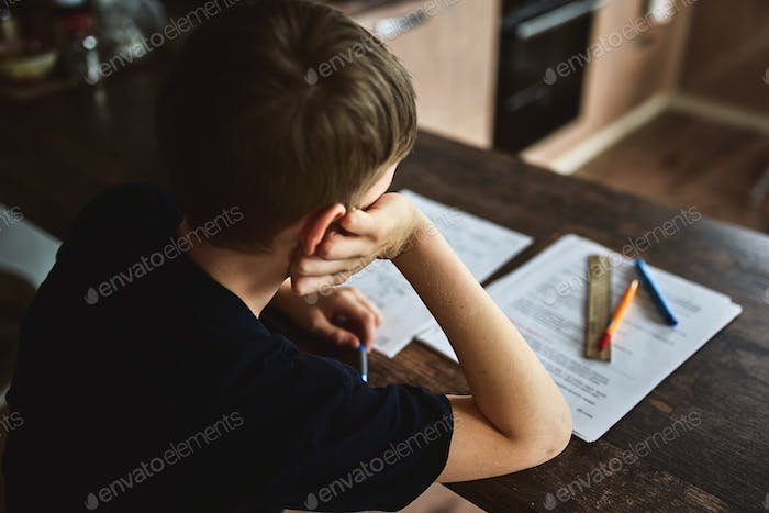 boy pupil sitting at the table and looking at the camera.  facial expression tired of lessons