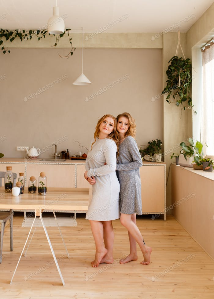 Two happy adult sisters blonde girlfriends in home clothes hug and have breakfast in an eco friendly
