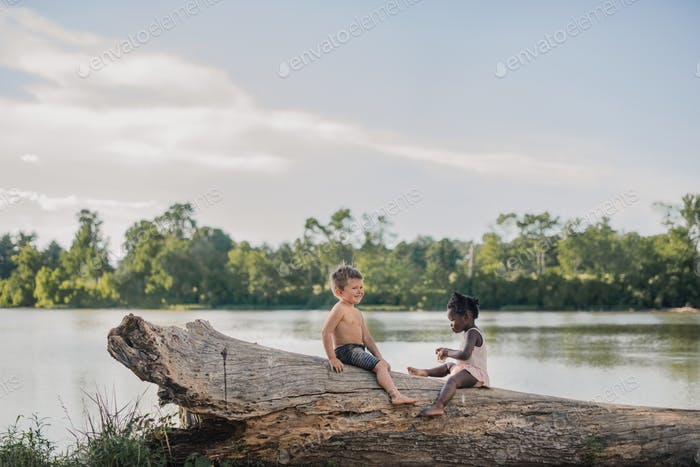 Diverse multiracial friends sitting on a log by a lake -kids having fun exploring outdoors in summer