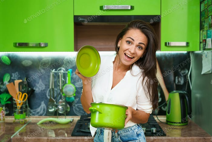 A young woman is holding a saucepan and smiling against
