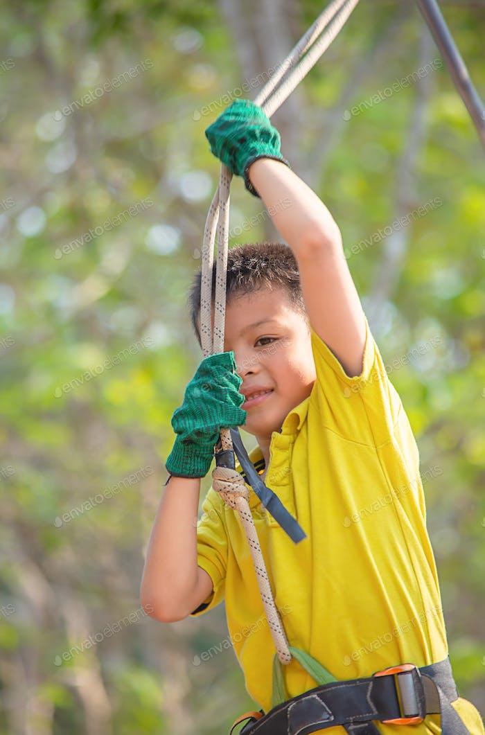 Asean Junge Knoten das Seil und lächelnd glücklich Hintergrund verschwommen Baum.