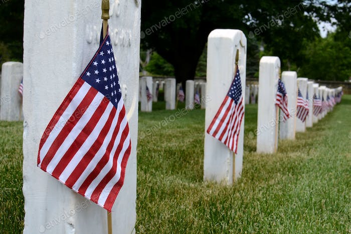 Rows of grave stones in a National cemetery decorated with American flags for Memorial Day.