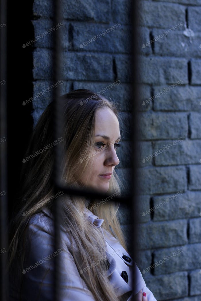 Portrait of a beautiful woman in a trench coat leaning on the loft brick wall deep in thought