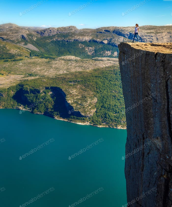 Young woman on rock over fjord in Norway