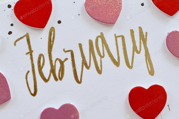 Februar in goldenen Buchstaben, umgeben von rosa und roten Herzen