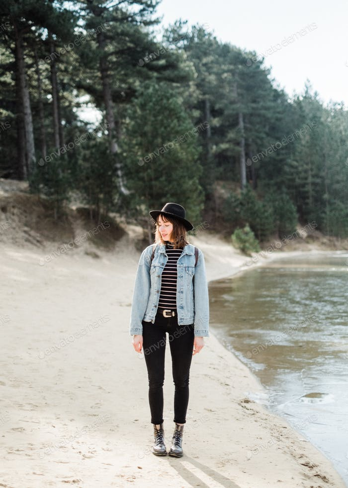 Young woman standing next to a lake, traveling solo. Hiking through the forest