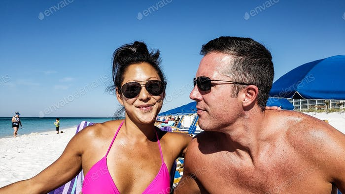 Millenial couple on vacation at the beach having a good time and very happy...