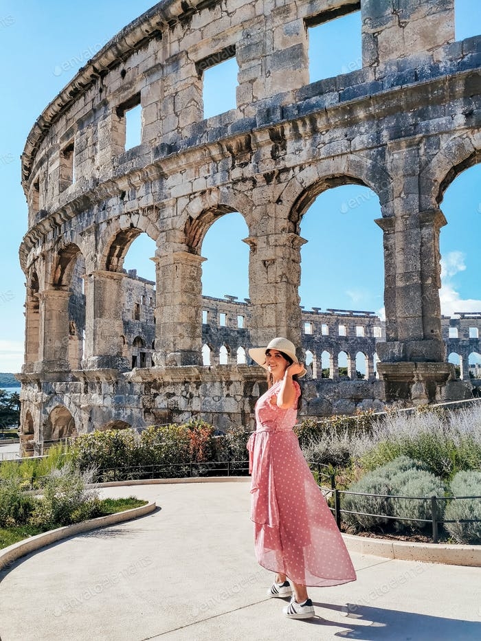 Beautiful young woman in pink dress in front of ancient roman arena