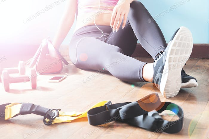 Female fitness resting and relaxing after workout. Woman sitting down on wood floor. Sport, Fitness,