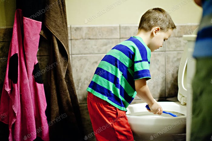 Boy cleans a toilet in a bathroom