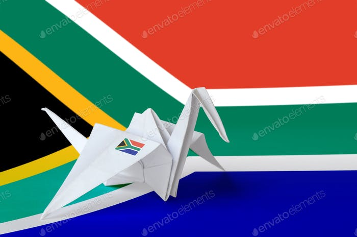 South Africa flag depicted on paper origami crane wing. Oriental handmade arts concept