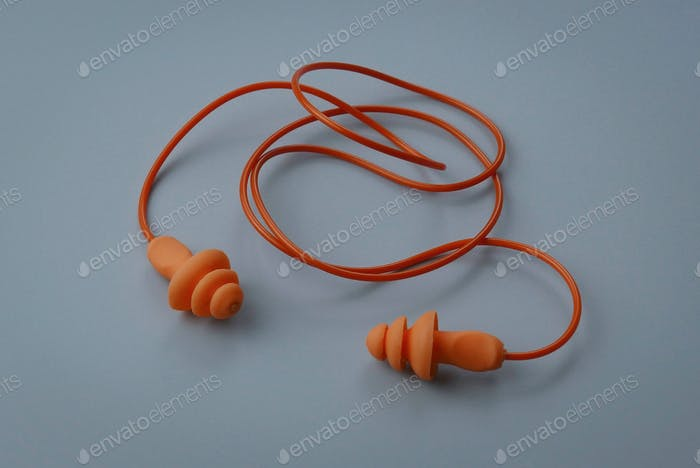 Yellow hearing safety protection earplug isolated on a grey background.