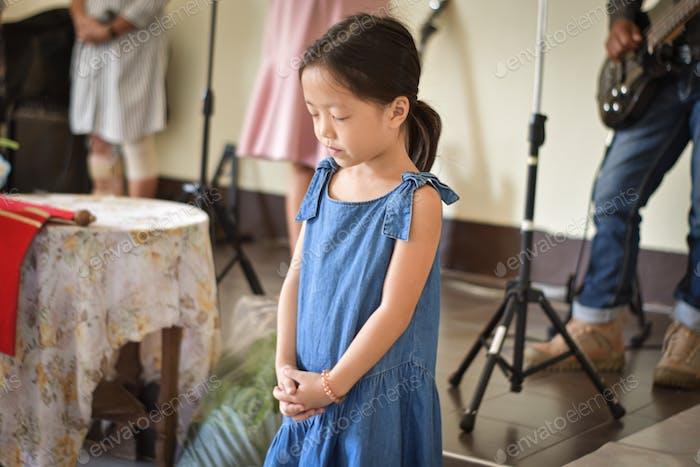 Religious christian girl praying in church