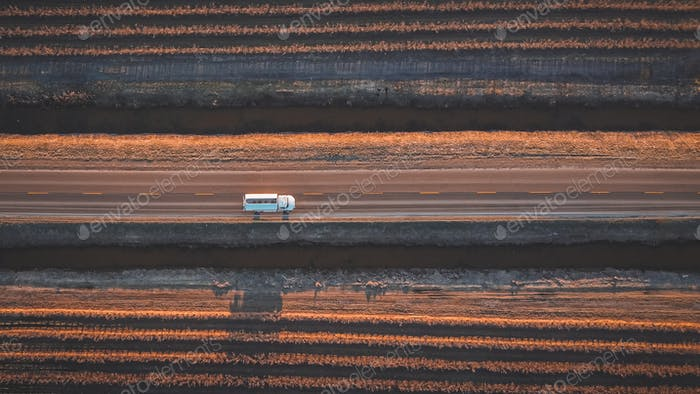 Aerial drone shot of a single white truck on a 2 lane rural road in the country.