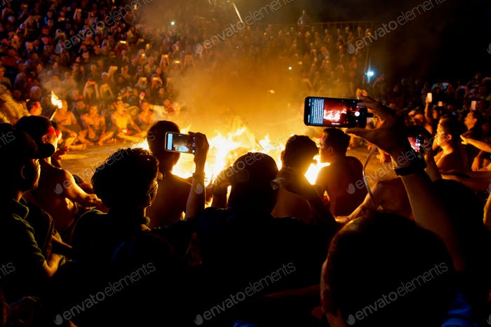 People and their photos of a Balinese Fire Dance. Uluwatu Temple, Bali.