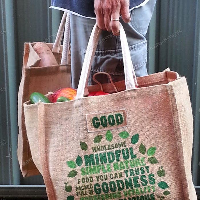 Seitenansicht der Person, die umweltfreundliche wiederverwendbare Lebensmittelbeutel mit frischen lokalen angebauten f