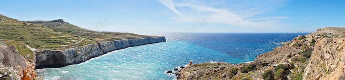 Panoramic view of Fomm Ir-Rih bay with blue water of the Mediterranean Sea and terraced fields