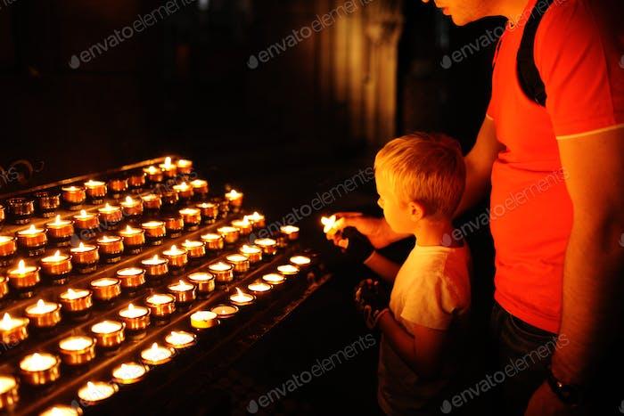 Ein kleiner blonder Junge und sein Vater zünden Kerzen in einer katholischen Kirche an