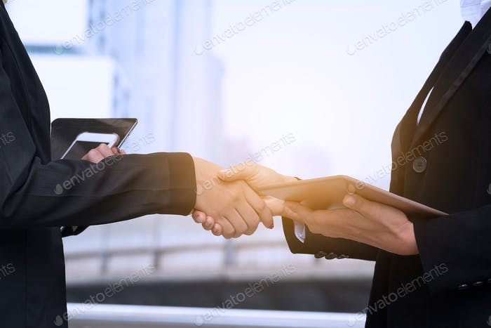Close up of women hand shaking with city view in the background.