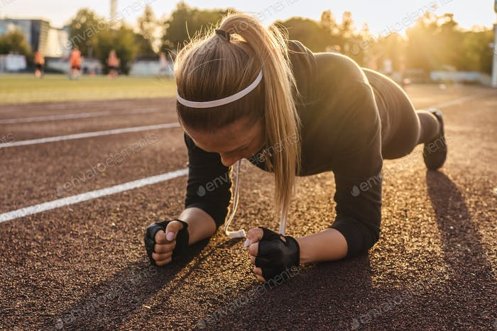 Young athletic woman doing plank exercise on running track. Sunset light on background, beautiful pe