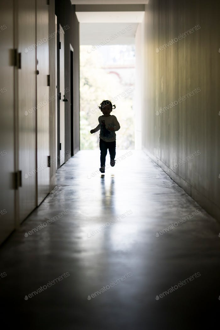 Young girl running down dark corridor towards the light and her exit. back lit with natural light fr