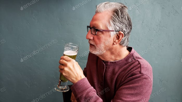 Profile of a distinguished man holding a glass of beer in hand with green background.