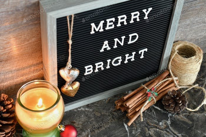 """Message Board saying """"Merry and Bright"""" with a lit candle & Christmas decorations"""