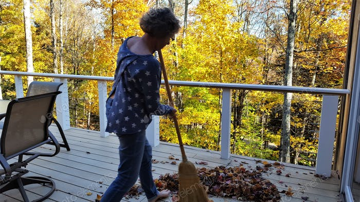Sweeping the leaves off the deck on a crisp fall day in New England.  People in Fall.