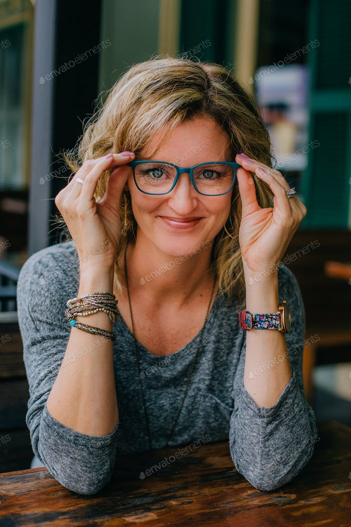 A professional woman in her 40s putting on a pair of trendy glasses.
