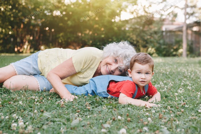 Grandmother playing with grandson on backyard home on sunny day
