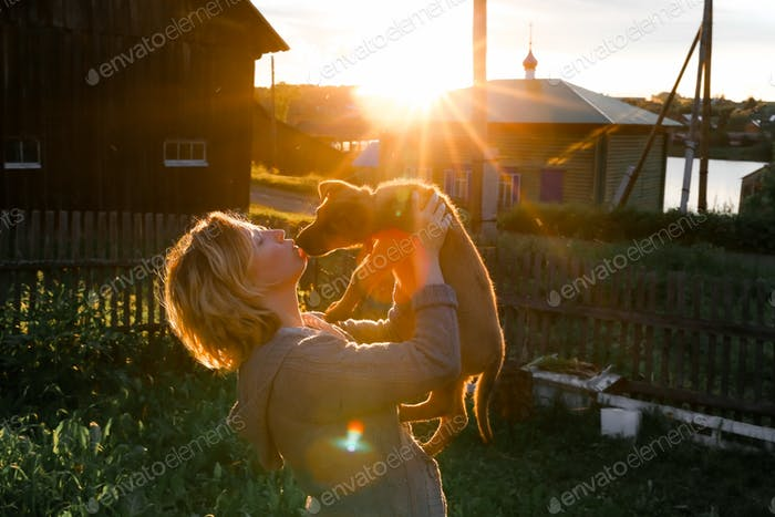 a young woman in a gray sweater holds a puppy in her arms and kisses him at sunset
