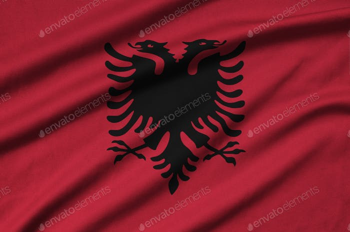 Albania flag  is depicted on a sports cloth fabric with many folds. Sport team waving banner