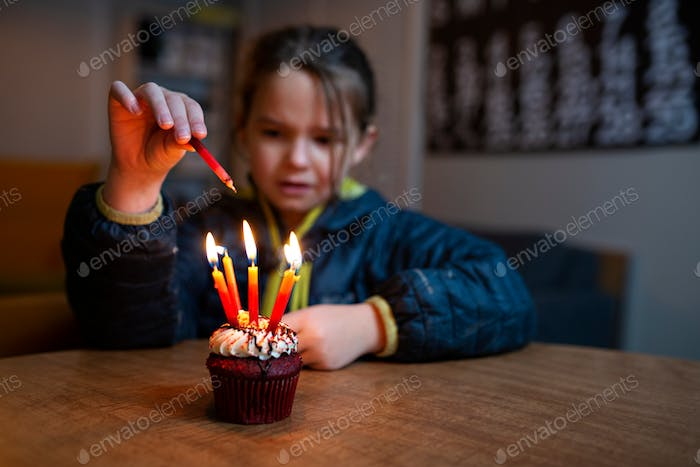 little girl lighting birthday candles