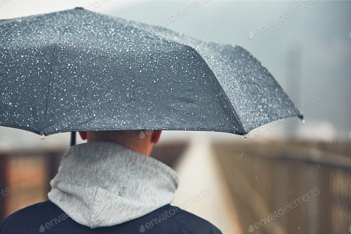 Man with umbrella in rain. Gloomy weather in city. Selective focus on the raindrop.