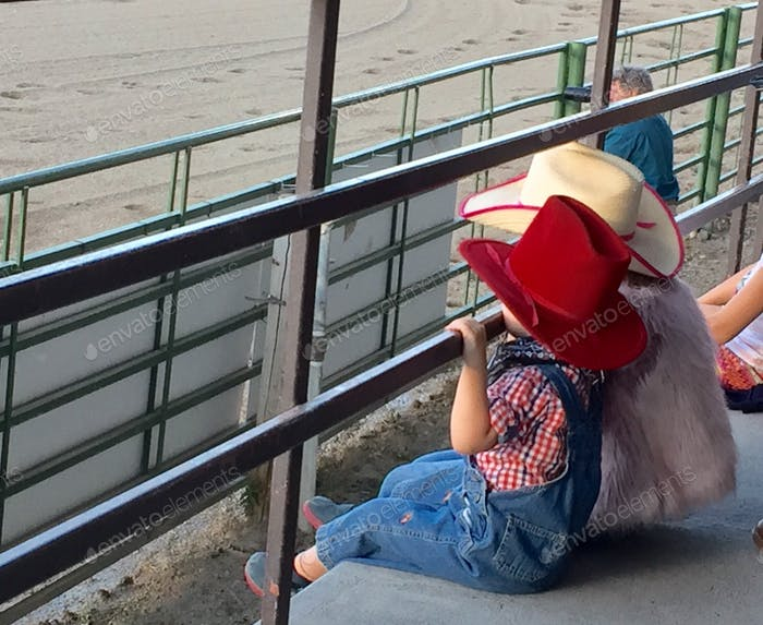 Two little children captivated at the rodeo