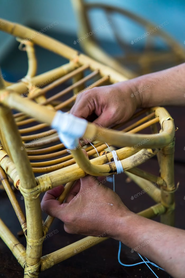 Hand tying a rope to the rattan chair. fixing and upcycling furniture.