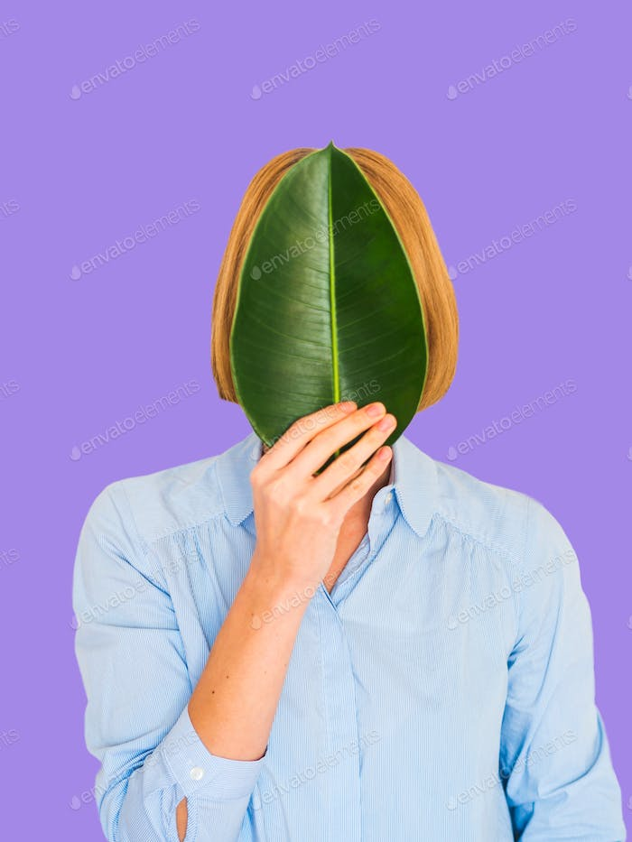 Young woman with face covered by a leaf on bold violet background