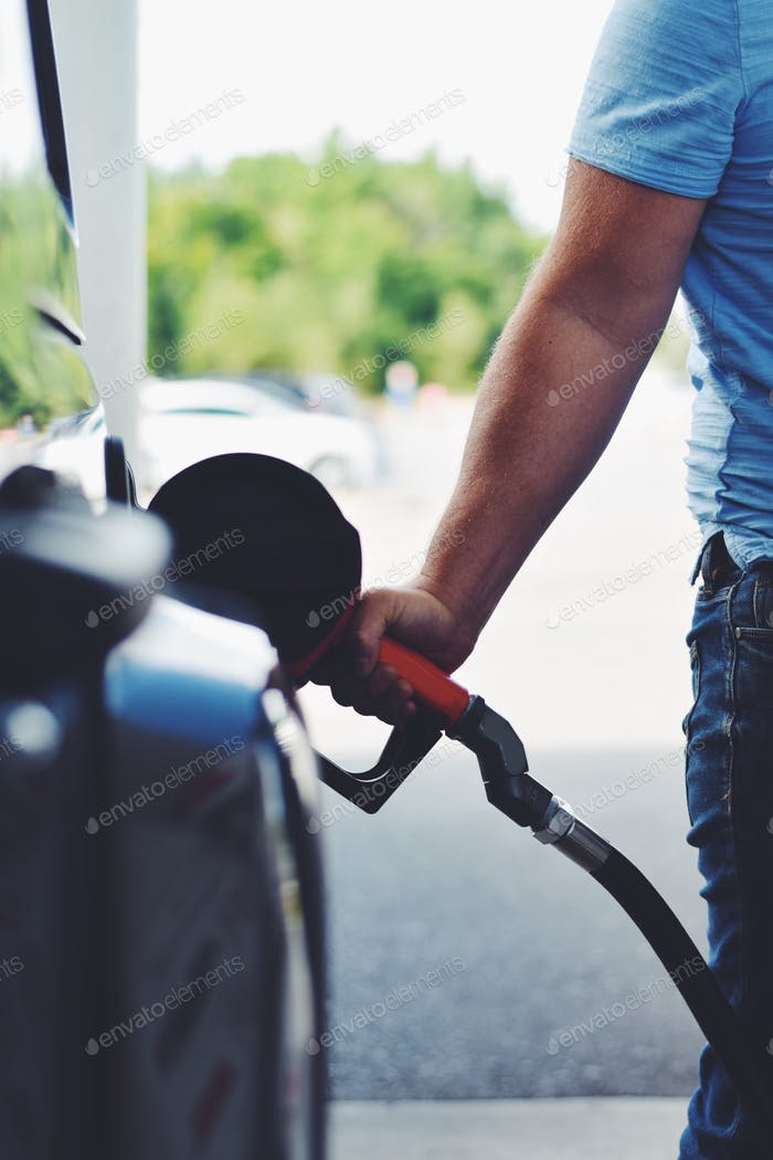 Man is refueling his car at a gas station