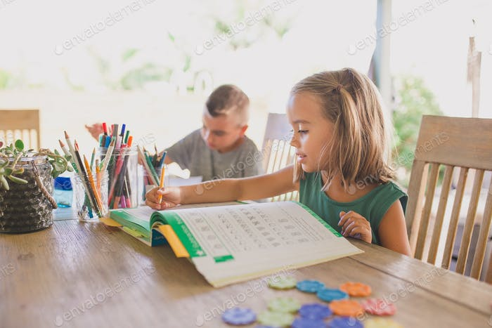 Little girl doing homeschool in backyard