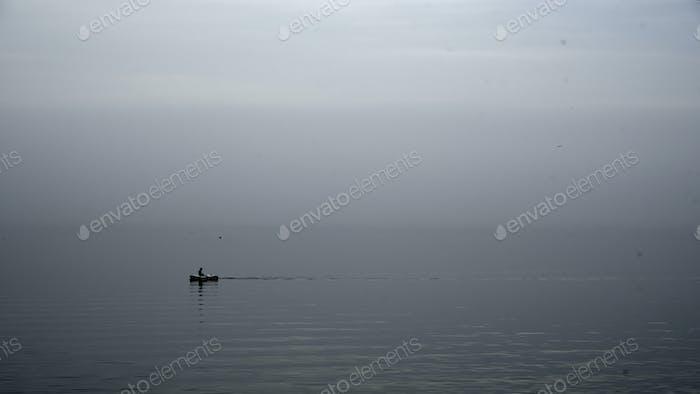 Row boat on gray foggy rainy morning day
