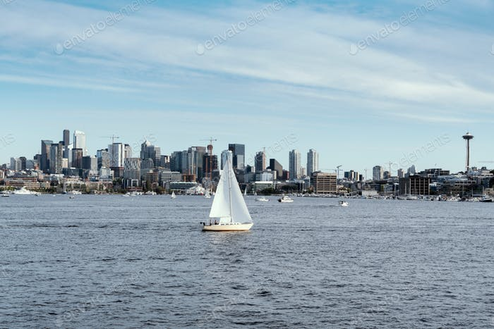 Sailboat at sail on Lake Union with Seattle skyline and Space Needle in the background.