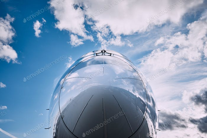 Reflection of clouds on airplane. Close-up view of cockpit against sky.