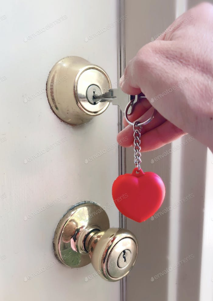 Woman homeowner unlocking & opening golden door knob at her home door with a key in a heart keychain