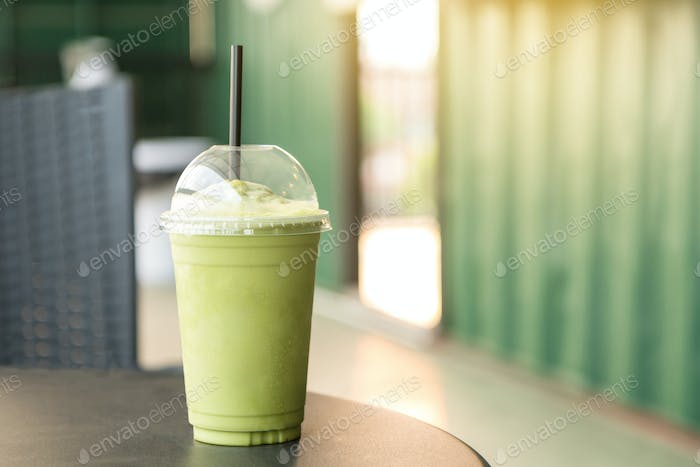 Green tea matcha smoothies in a plastic cup. Interior coffee shop. Condensation on a cup